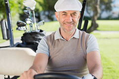 Happy golfer driving his golf buggy smiling at camera Stock Photos