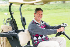 Happy golfer driving his golf buggy smiling at camera Royalty Free Stock Image