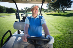 Happy golfer driving his golf buggy Royalty Free Stock Photos