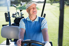 Happy golfer driving his golf buggy Stock Photography