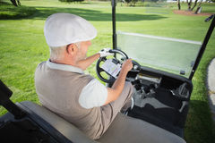 Happy golfer driving his golf buggy Stock Photo