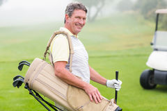 Happy golfer with golf buggy behind Stock Photo