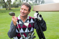 Happy golfer beside his golf buggy Stock Photo