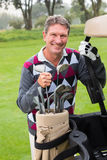 Happy golfer beside his golf buggy. On a sunny day at  the golf course Royalty Free Stock Image