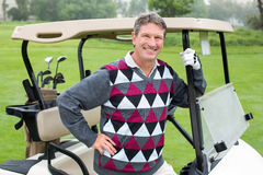 Happy golfer beside his golf buggy Stock Image
