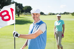 Happy golfer holding eighteenth hole flag with partner behind him. On a sunny day at the golf course Stock Photos