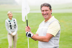 Happy golfer holding flag for cheering partner. On a foggy day at the golf course Stock Photography