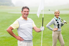 Happy golfer holding flag for cheering partner. On a foggy day at the golf course Royalty Free Stock Photos