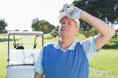 Happy golfer looking at camera with golf buggy behind Royalty Free Stock Photo