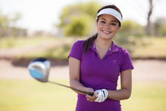 Happy golfer ready to play. Cute Hispanic female golfer holding a golf club with both hands and smiling Stock Photo