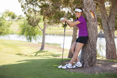 Happy golfer relaxing under a tree Stock Photos