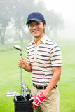 Happy golfer taking club from golf bag Stock Image