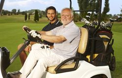 Happy golfers in golf cart. Happy golfers sitting in golf cart, smiling, looking at camera royalty free stock images