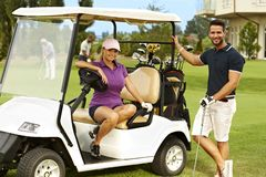 Happy golfers and golf cart. Happy golfers sitting in golf cart, smiling, looking at camera stock photos