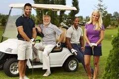 Happy golfers ready to play. Happy team of golfers ready to play, standing and sitting around golf cart, smiling, looking at camera Royalty Free Stock Image