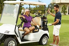 Happy golfers talking in golf cart. Happy male and female golfers talking on the fairway in golf cart royalty free stock image