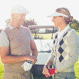 Happy golfing couple chatting with golf buggy behind. On a sunny day at the golf course stock photography