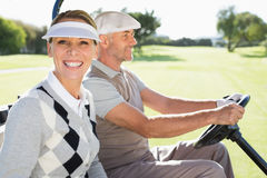 Happy golfing couple driving in their buggy Royalty Free Stock Image