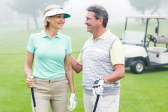 Happy golfing couple facing each other with golf buggy behind. On a foggy day at the golf course royalty free stock images
