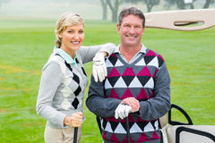 Happy golfing couple with golf buggy behind. On a foggy day at the golf course stock photography