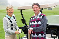 Happy golfing couple with golf buggy behind Royalty Free Stock Photos