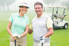 Happy golfing couple with golf buggy behind. On a foggy day at the golf course stock image