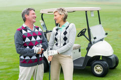 Happy golfing couple with golf buggy behind. On a foggy day at the golf course stock photos
