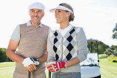 Happy golfing couple with golf buggy behind Royalty Free Stock Photo