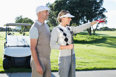 Happy golfing couple looking at course with golf buggy behind. On a sunny day at the golf course royalty free stock image