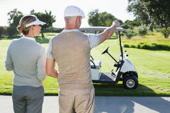 Happy golfing couple looking out to the course Royalty Free Stock Images