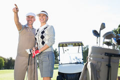 Happy golfing couple pointing with golf buggy behind Stock Image