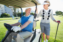 Happy golfing couple setting out for the day on buggy Royalty Free Stock Photos