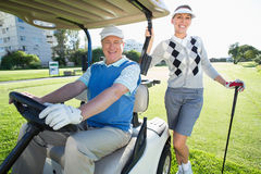 Happy golfing couple setting out for the day on buggy Royalty Free Stock Photo