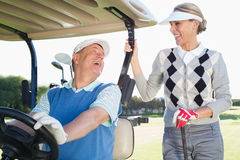 Happy golfing couple setting out for the day on buggy. On a sunny day at the golf course stock photography