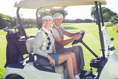 Happy golfing couple sitting in buggy smiling at camera. On a sunny day at the golf course royalty free stock images
