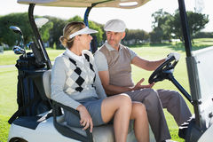 Happy golfing couple sitting in buggy smiling at each other Stock Images