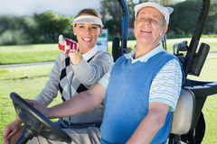 Happy golfing couple sitting in golf buggy looking around Royalty Free Stock Photography