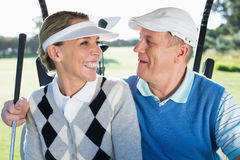 Happy golfing couple sitting in golf buggy smiling at each other Stock Photo