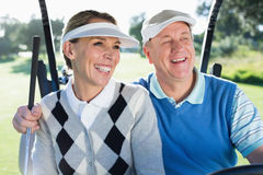 Happy golfing couple sitting in golf buggy smiling Stock Images