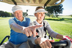 Happy golfing couple sitting in golf buggy Royalty Free Stock Photography