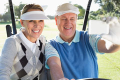 Happy golfing couple sitting in golf buggy taking a selfie Stock Images