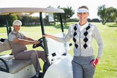 Happy golfing couple smiling at camera with their buggy Royalty Free Stock Photo