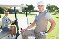Happy golfing couple smiling at camera with their buggy. On a sunny day at the golf course stock images