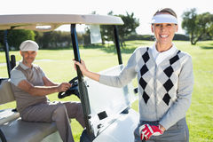 Happy golfing couple smiling at camera with their buggy Royalty Free Stock Photography