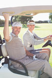 Happy golfing couple smiling at camera in their buggy Royalty Free Stock Photography