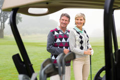Happy golfing couple smiling. On a foggy day at the golf course Stock Photos