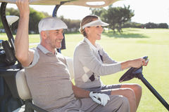 Happy golfing couple smiling in their buggy. On a sunny day at the golf course royalty free stock images