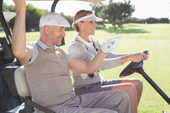 Happy golfing couple smiling in their buggy Stock Photo