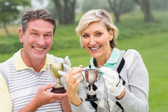 Happy golfing couple with trophy. On a foggy day at the golf course Stock Images