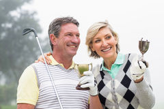 Happy golfing couple with trophy. On a foggy day at the golf course Stock Photos